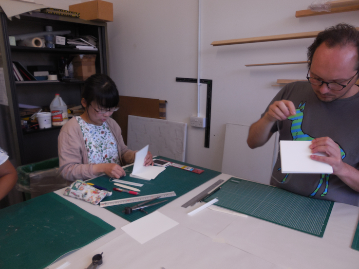 Students sewing books